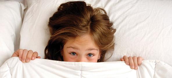 Kind onder een dekbed kijkt angstig in de lens